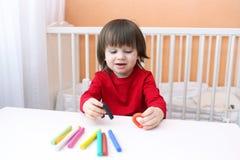 2 años preciosos de muchacho en camisa roja con el playdough Foto de archivo libre de regalías