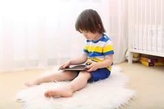 2 años preciosos de muchacho en camiseta rayada con la tableta Imagen de archivo
