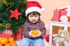 2 años preciosos de muchacho en el sombrero de Papá Noel con la mandarina Imágenes de archivo libres de regalías