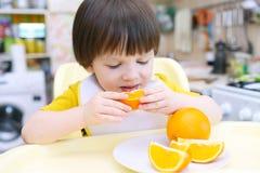 2 años preciosos de muchacho que come la naranja Imagenes de archivo