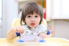 2 años preciosos de muchacho que come la sopa Foto de archivo