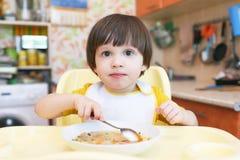 2 años preciosos de muchacho que come la sopa Imagenes de archivo