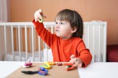 2 años preciosos de muchacho que juega con plasticine en casa Imagen de archivo libre de regalías