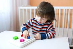 2 años preciosos de muchacho que juega el clasificador de la forma Imágenes de archivo libres de regalías