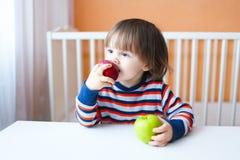 2 años preciosos de niño que come manzanas Foto de archivo