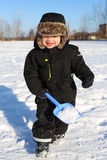 2 años preciosos de niño que corre con la pala en invierno Imagen de archivo