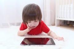 2 años preciosos lindos de muchacho en camiseta roja con la tableta Imágenes de archivo libres de regalías