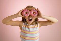Años rubios felices y emocionados hermosos jovenes de la muchacha 8 o 9 que sostienen dos anillos de espuma en sus ojos que miran Imagen de archivo