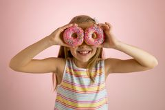 Años rubios felices y emocionados hermosos jovenes de la muchacha 8 o 9 que sostienen dos anillos de espuma en sus ojos que miran Fotos de archivo
