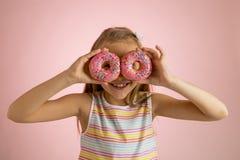 Años rubios felices y emocionados hermosos jovenes de la muchacha 8 o 9 que sostienen dos anillos de espuma en sus ojos que miran Imágenes de archivo libres de regalías