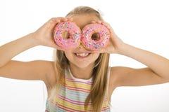 Años rubios felices y emocionados hermosos jovenes de la muchacha 8 o 9 que sostienen dos anillos de espuma en sus ojos que miran Foto de archivo libre de regalías
