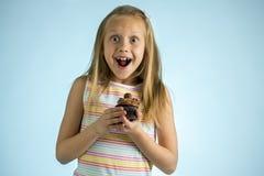 Años rubios felices y emocionados hermosos jovenes de la muchacha 8 o 9 que sostienen la torta de chocolate en su mano que parece Fotos de archivo