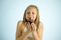 Años rubios felices y emocionados hermosos jovenes de la muchacha 8 o 9 que sostienen la torta de chocolate en su mano que parece Fotos de archivo libres de regalías