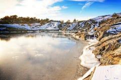Aúlle con el muelle rodeado por la costa rocosa en invierno Foto de archivo libre de regalías