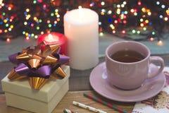 Aún una vida festiva con una taza de té, de una caja de regalo y de velas ardientes Fotos de archivo