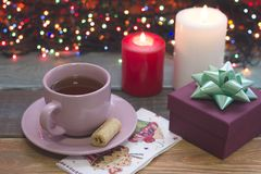 Aún una vida festiva con una taza de té, de una caja de regalo y de velas ardientes Imagen de archivo libre de regalías