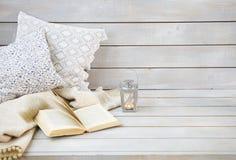 Aún vida acogedora con la linterna, las almohadas, el libro y la tela escocesa Fotografía de archivo libre de regalías
