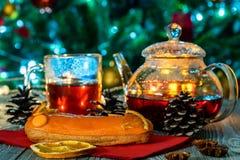 Aún vida acogedora con té, luz de la vela y eclairs Imagen de archivo