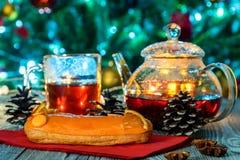 Aún vida acogedora con té, luz de la vela y eclairs Fotografía de archivo