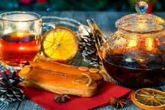 Aún vida acogedora con té, luz de la vela y eclairs Foto de archivo