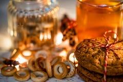Aún vida acogedora del té, de la luz de la Navidad y de los pasteles Imágenes de archivo libres de regalías