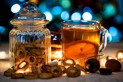Aún vida acogedora del té, de la luz de la Navidad y de los pasteles Imagen de archivo