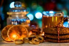 Aún vida acogedora del té, de la luz de la Navidad y de los pasteles Imagen de archivo libre de regalías