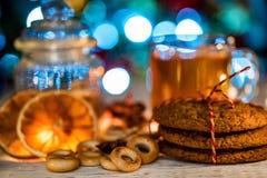 Aún vida acogedora del té, de la luz de la Navidad y de los pasteles Fotos de archivo
