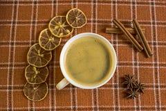 Aún vida anaranjada y blanca con una taza de café, canela, verum del illicium en tela a cuadros Foto de archivo