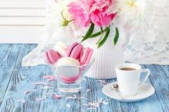 Aún vida artística con las peonías y la taza de café y de pétalos Imagen de archivo libre de regalías