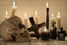Aún vida asustadiza con el cráneo, las velas ardientes y la cruz Foto de archivo