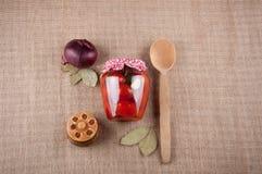 Aún vida auténtica Los tomates en tarro, cebollas, pan, caja de madera, bahía se van en fondo de la harpillera Foto de archivo libre de regalías