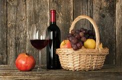 Aún-vida. Botella de vino, de vidrio y de cesta con la fruta Imagen de archivo