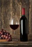 Aún-vida. Botella de vino rojo, de vidrio y de uvas Foto de archivo