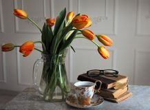 Aún-vida clásica con los libros y tulipanes y una taza de té Fotos de archivo libres de regalías