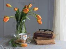 Aún-vida clásica con los libros y tulipanes y una taza de té Imagen de archivo libre de regalías