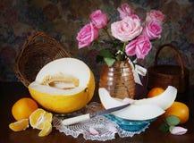 Aún vida clásica con un melón y las flores en un florero Fotografía de archivo libre de regalías