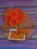 Aún vida colorida con un florero y las naranjas en un mantel rayado Foto de archivo libre de regalías