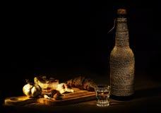 Aún-vida con el tocino, ajo, pan, vodka Foto de archivo libre de regalías