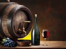 Aún-vida con el vidrio del vino, de la botella y del barril Imagen de archivo