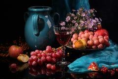 Aún-vida con el vino, la fruta y un jarro azul marino en un backg negro Foto de archivo