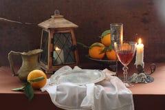 Aún-vida con el vino rojo en un vidrio, naranjas y una linterna vieja Foto de archivo