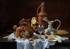 Aún-vida con el vino rojo, la fruta y una gallina una parrilla Imagen de archivo