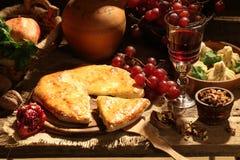 Aún-vida con el vino rojo, una empanada con queso y la fruta Imagenes de archivo