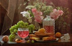 Aún-vida con el vino y fruta rosada, tortas planas y gladiolos Foto de archivo