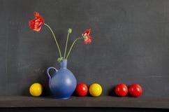 Aún-vida con la amapola y las bolas coloridas Imágenes de archivo libres de regalías