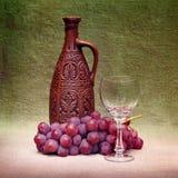 Aún-vida con la botella, el vidrio y las uvas de la arcilla Imagen de archivo libre de regalías