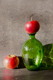 Aún-vida con la botella y dos manzanas Imágenes de archivo libres de regalías