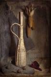 Aún-vida con la botella y el maíz trenzados en estilo retro Fotografía de archivo libre de regalías
