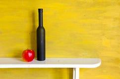 Aún-vida con la botella y la manzana negras Foto de archivo libre de regalías